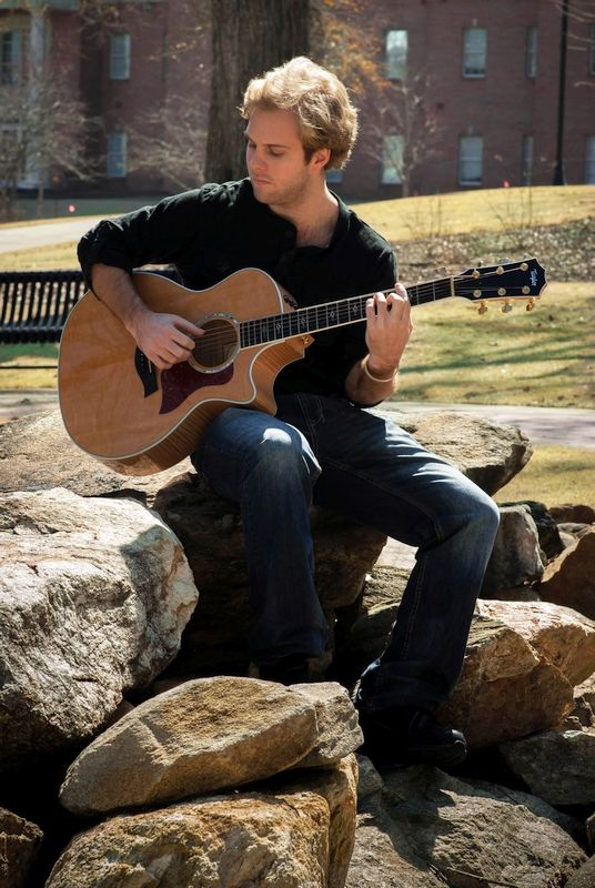 Wyatt sitting playing guitar on rock garden